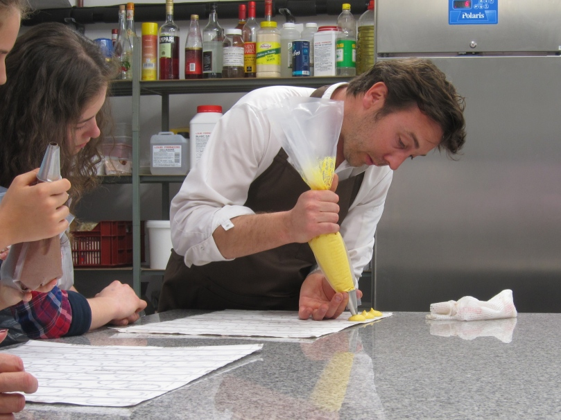 Nicolas demonstrating the art of piping macaron shells