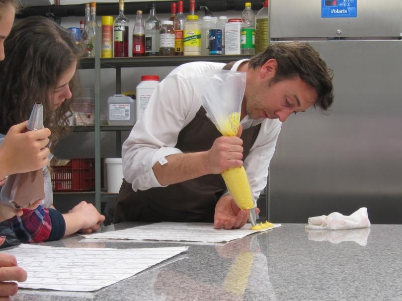 Nicolas demonstrating the art of piping macaron shells